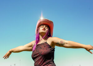 Photograph of a woman wearing a pink cowboy hat with her arms spread out to her sides.